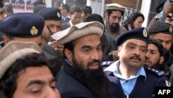 Pakistani security personnel escort Zaki-ur-Rehman Lakhvi (C) during a court appearance in December.