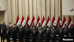 Iraq's new government stands for an oath at the house of parliament in Baghdad on December 21.