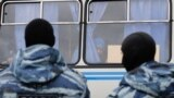 Russia - Migrant worker looks out of a police vehicle, OMON