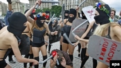 """Members of the activist group FEMEN, dressed in scanty """"riot police"""" outfits, pretend to beat up a reporter during a rally against censorship and repression in the Ukrainian media."""