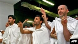 Iranian President Mahmud Ahmadinejad (center) throws stones at a column symbolizing the devil in Mecca.