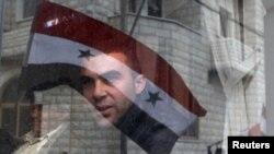 Reflektimi i falmurit të Sirisë në një dritare, ku shihet një djalë duke i shikuar protestat/ foto nga arkivi.