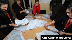 Members of a local electoral commission count ballots at a polling station after a snap parliamentary election in Baku on February 9.