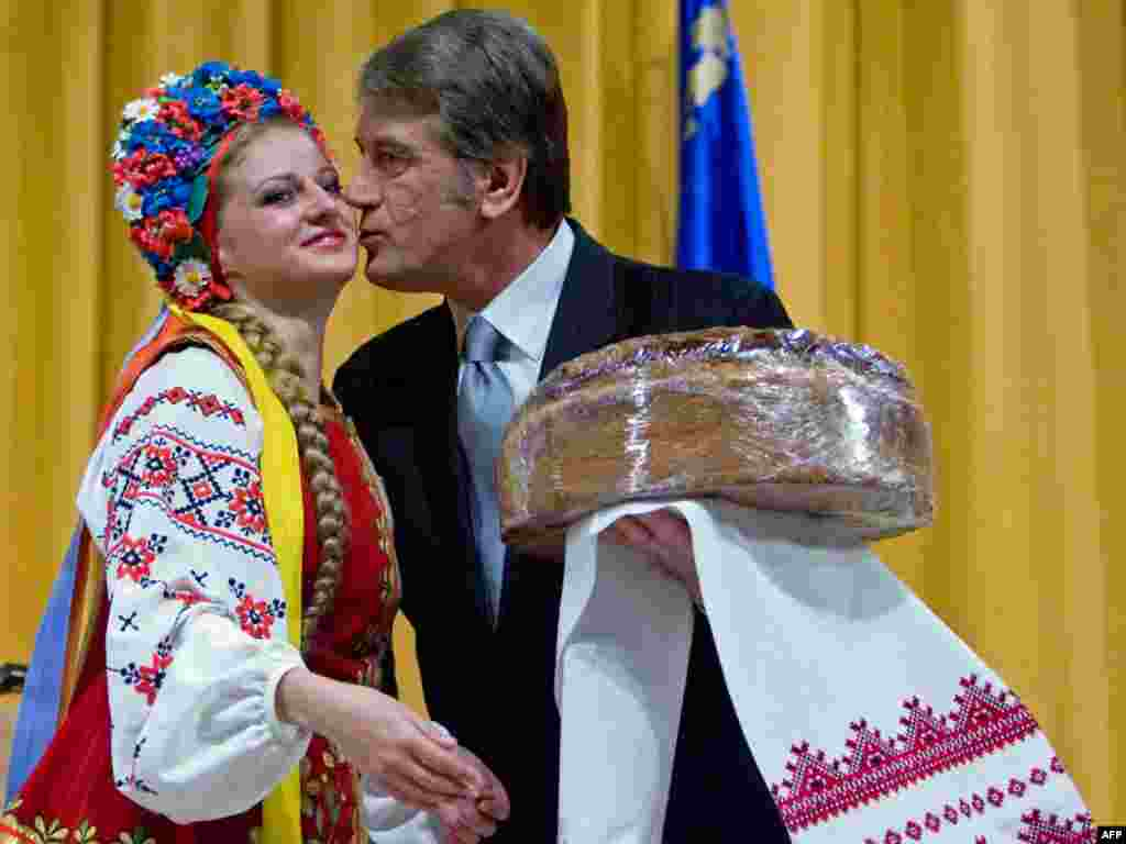 Ukrainian President Viktor Yushchenko kisses a woman in traditional dress while campaigning in the city of Cherkasy. - Ukraine is gearing up for its presidential election on January 17. Polls shows President Yushchenko trailing behind Prime Minister Yulia Tymoshenko and Viktor Yanukovych. Photo by Myshko Markiv for AFP
