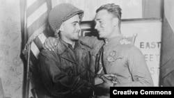 Счастливые 2-й лейтенант У.Робертсон и лейтенант А. С. Сильвашко на фоне надписи «Восток встречается с Западом».