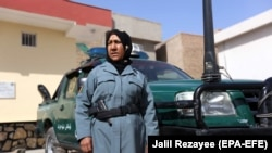 FILE: An Afghan female police officer stands guard outside a police station in Herat (October 2017).
