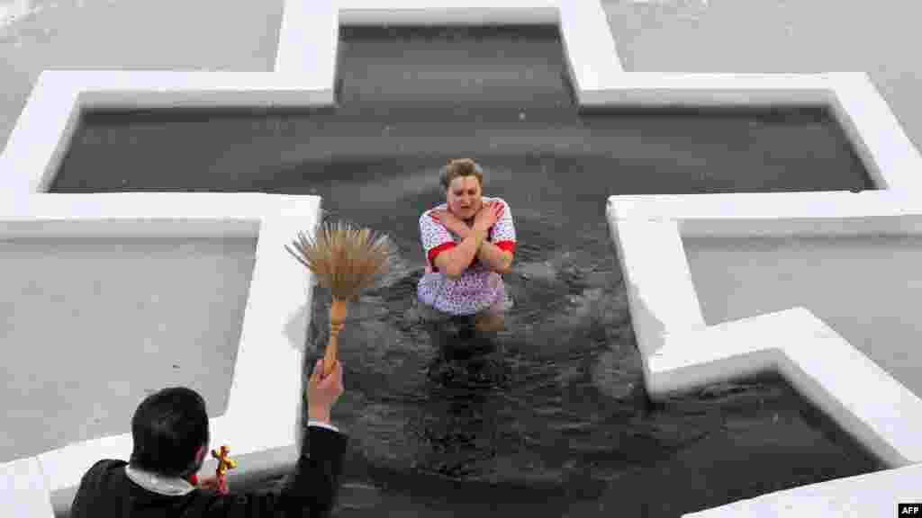 Credincioși ortodocși înoată în apa rece ca ghiața la Minsk pe 18 ianuarie pentru a celebra Epifania. (AFP/Victor Dracev)
