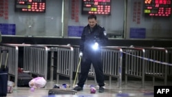 Полицейский в здании вокзала города Куньминь, где произошло нападение.