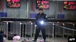 Қытай полицейі теміржол станциясында шабуыл жасалған жерді тексеріп тұр. Қытай, Куньмин, 1 наурыз 2014 жыл.
