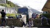 Un grup de migranți, așteptând trenul la granița dintre Italia și Germania