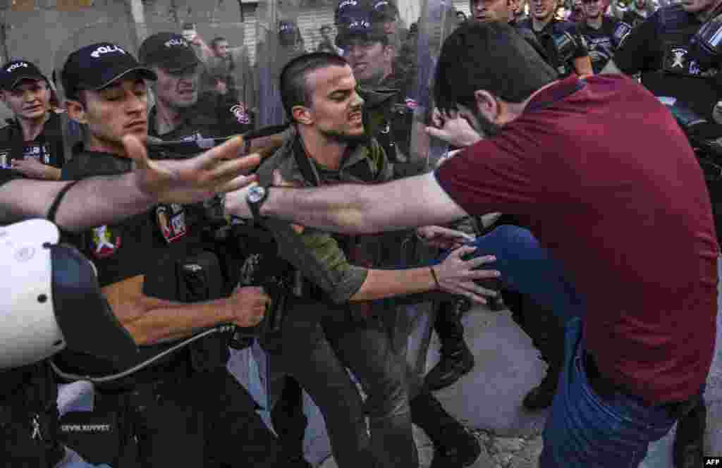 A plainclothes police officer kicks a member of a group of LGBT rights activist as Turkish police prevent them from going ahead with a gay-pride annual parade in Istanbul on June 25. (AFP/Bulent Kilic)