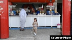 Abdrakhman in fatigues outside a Mosul juice bar