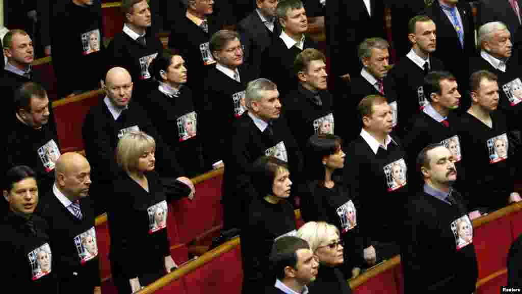 Members of the Batkivshchina (Fatherland) bloc, wearing shirts with a portrait of their leader, imprisoned former Prime Minister Yulia Tymoshenko, listen to the state anthem before the first session of the newly elected parliament in Kyiv. (Reuters/Anatolii Stepanov)