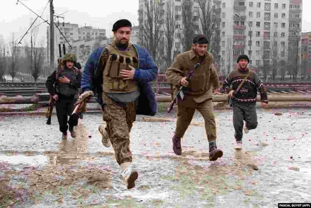 Грозный бомбили интенсивно и круглосуточно. Президентский дворец был разрушен. На фотографии чеченские бойцы бегут от одногоразрушенного домак другому. 12 января 1995 года