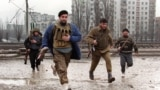 RUSSIA - Chechen fighters run across the street, trying to avoid sniper fires as they head for the presidential palace in dowtown Grozny on January 12, 1995