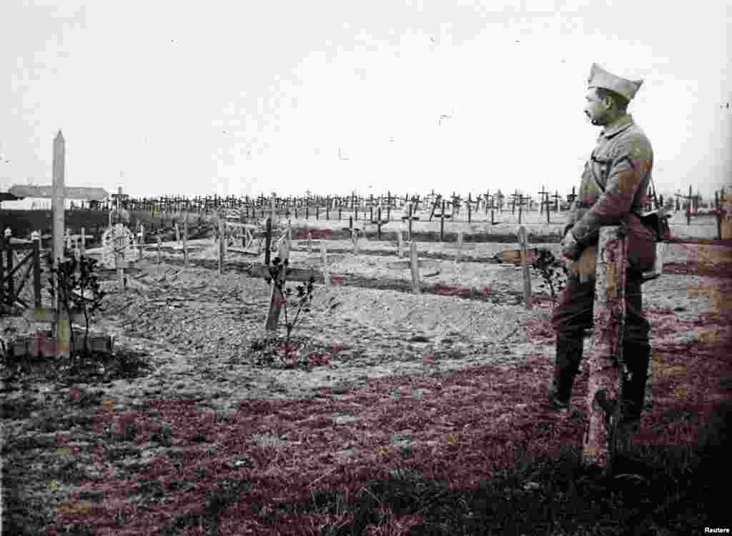 A French officer stands near the fresh graves of soldiers killed at Saint-Jean-sur-Tourbe on the Champagne front in eastern France, December 19, 1916.