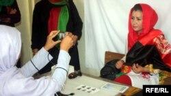Сайлауда дауыс беруге құқық беретін куәлік алу үшін суретке түсіп жатқан әйел. Кабул, 3 қазан 2013 жыл.