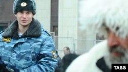 Сотрудник полиции рядом с мужчиной c Северного Кавказа.