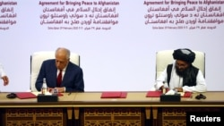 Спецпредставник США Залмай Халілзад (л) і голова делегації талібів мулла Абдул-Гані Барадар (п) підписують угоду, Доха, 29 лютого 2020 року
