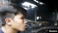 Валензуэладагы фабриканын өрттө тирүү калган жумушчусу тилсиз жоо кыйраткан ишкананы карап турат. Манила, 14-май 2015.