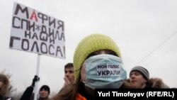"The rallies in Moscow on December 10 protesting the election results were said to be the largest demonstrations since the collapse of the Soviet Union. Her mask says ""They stole my vote."" The banner says ""The Mafia Stole Our Vote."""