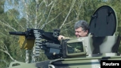 Ukrainian President Petro Poroshenko tries out a tank on July 26.