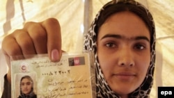 A woman shows her voter registration card in Parwan Province