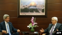 U.S. Secretary of State John Kerry (left) meets with Palestinian Authority President Mahmud Abbas on July 19 at the Mukataa compound in the West Bank city of Ramallah.