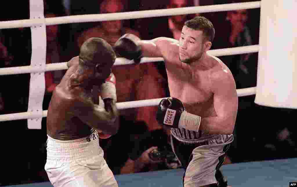 OCTOBER 30, 20212 -- Afghan-German boxer Hamid Rahimi (right) throws a punch at Tanzania's Said Mbelwa in Afghanistan's first professional bout in 30 years. Rahimi won the World Boxing Organization's unclaimed intercontinental middleweight championship by TKO in the seventh round before some 1,500 spectators in Kabul. (AFP/Massoud Hossaini)