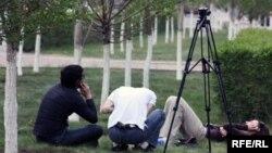 Телевизионные журналисты на траве в ожидании развязки события. Иллюстративное фото. Астана, 17 мая 2010 года.