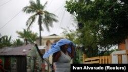 Një grua duke ecur nëpër shi derisa uragani Irma i kishte goditur Karaibet
