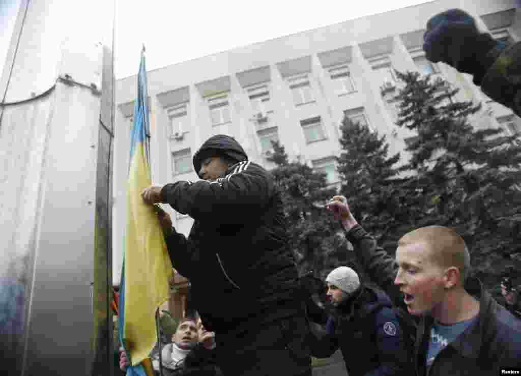 Rusiye tarafdarları Aqmescit şeer şurası yanındaki Ukraina bayrağını tüşüreler. 2014 senesi fevral 27 künü