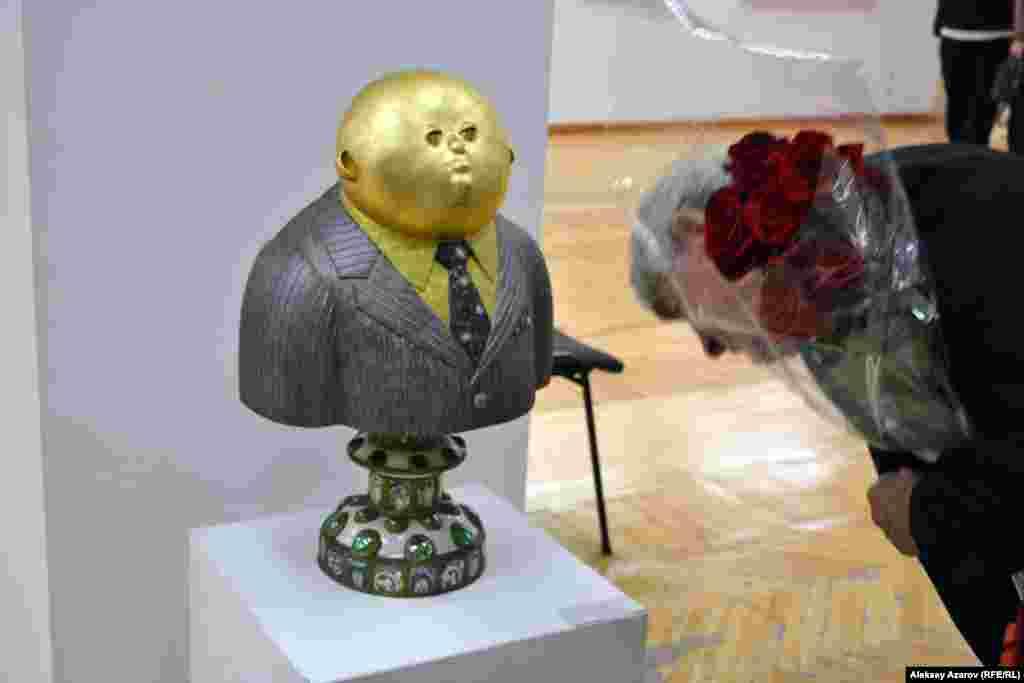 Работа Шамиля Гулиева «Золотой человек», вызывавшая морепозитивных эмоций у тех, кто ее рассматривал. Среди работ этогохудожника немало таких, которые несут иронию. В этой новой работепоказан собирательный образ одного из продуктов 25-летия независимости. Какие-то женщины при обсуждении этой скульптурыупотребили слово «буржуин». Это может быть образ и современногопредпринимателя, и современного чиновника.