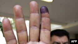 رجل يلوح بيده بعد الإدلاء بصوته في بغداد