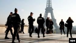 Эйфель мұнарасы маңында жүрген полиция өкілдері мен жай адамдар. Париж, 23 қараша 2015 жыл. (Көрнекі сурет.)