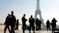 French Police officers patrol near the Eiffel tower in Paris shortly after the deadly attacks in the city that killed scores of people.
