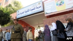 Egyptians stand in line outside a school turned into a polling station in Mansura, 120 kilometers north of Cairo.