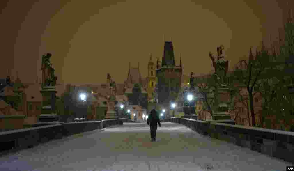 A man crosses the snow-covered Charles Bridge in Prague. (AFP/Michal Cizek)