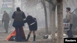Мариупольдегі зымыран шабуылынан қаза тапқан адамның денесін тексеріп жатқандар. Украина, 24 қаңтар 2015 жыл.
