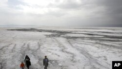 A family walks on the solidified salts of Lake Orumieh.