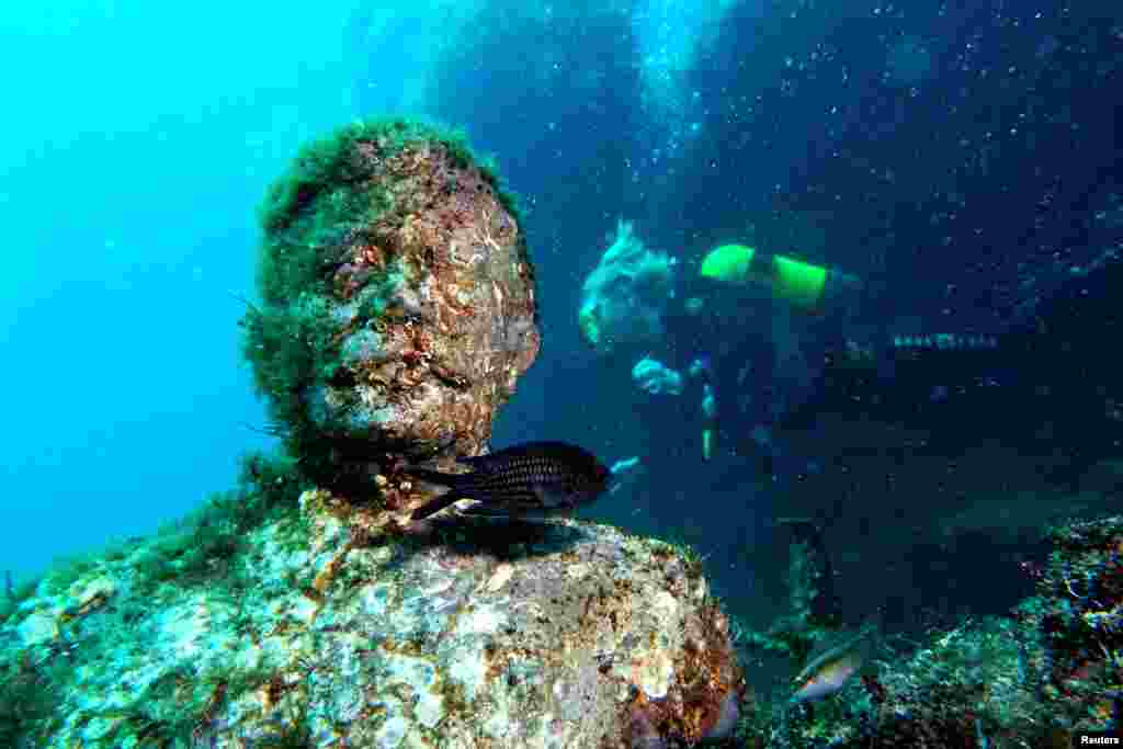 "A diver drifts past a bust of Josef Stalin. Andrey Nekrasov, one of the first to photograph the monuments, told RFE/RL the project began after the collapse of the U.S.S.R., when Soviet statues were being discarded and destroyed. The reviled sculptures were placed underwater ""away from vandals' hands."""