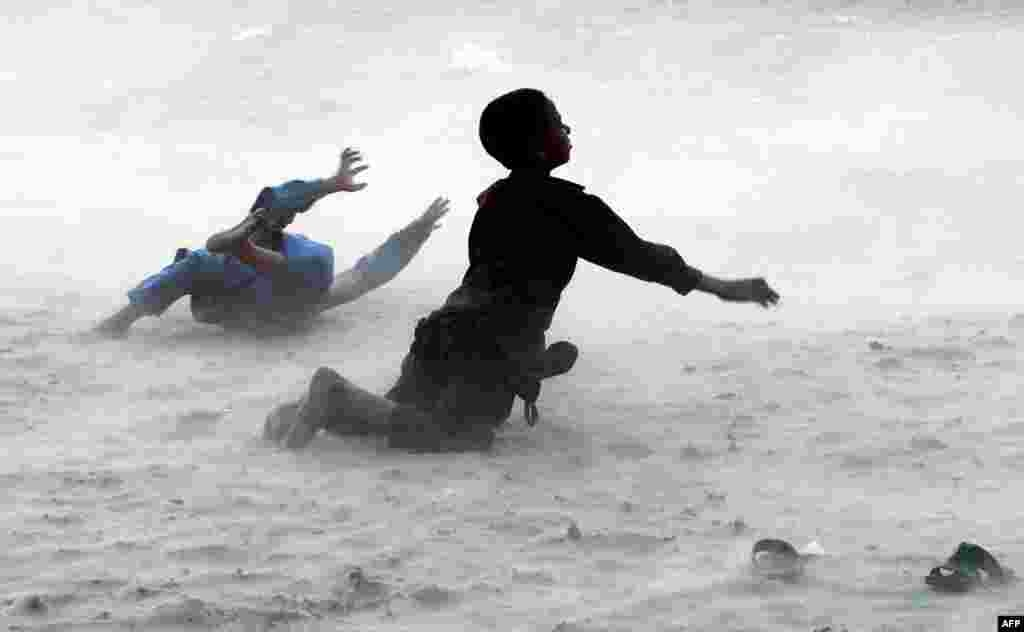 Children play during a dust storm on the banks of the Ravi River on the outskirts of Lahore, Pakistan. (AFP/Arif Ali)
