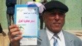 النجف: مواطن يمسك الدستور العراقي