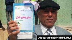 مواطن من النجف يتقدم تظاهرة ويحمل الدستور العراقي