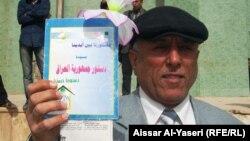 مواطن في النجف يحمل الدستور العراقي
