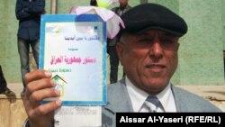 رجل يحمل نسخة من الدستور العراقي في إحتجاج بالنجف