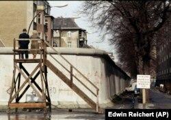 Западноберлинская пара смотрит на кварталы Восточного Берлина со специально установленной платформы в районе Нойкельн, апрель 1983 года.