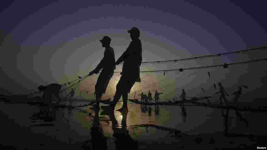 Pakistani fishermen are silhouetted against the setting sun as they pull in their nets to retrieve their catch at Karachi's Clifton Beach on May 23. (Reuters/Athar Hussain)