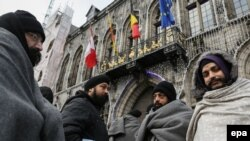 Asylum seekers from Afghanistan wrap themselves in blankets outside the Grand Place in Mons, Belgium, on December 23.