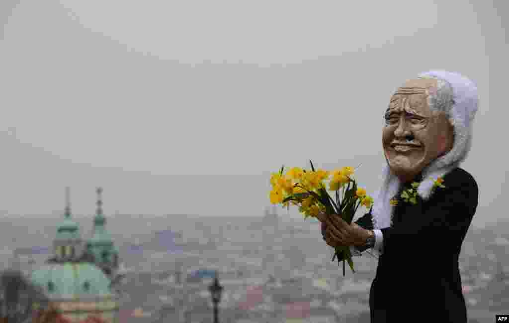 A man wearing a mask of Czech President Vaclav Klaus holds flowers during a march in Prague celebrating the end of his presidency. (AFP/Michal Cizek)